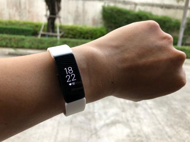 แขนข้างซ้าย กำลังสวม Fitbit Inspire HR อยู่ หน้าปัดบอกเวลา 18:22 หัวใจเต้น 92 ครั้งต่อนาที