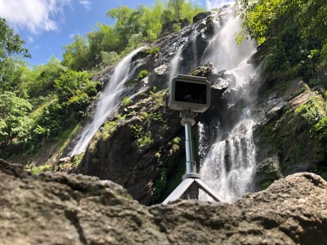 กล้อง GoPro Hero 7 Black Limited Edition พร้อมขาตั้ง Shorty วางอยู่บนโขดหิน โดยมีวิวด้านหลังเป็นน้ำตกคลองลาน