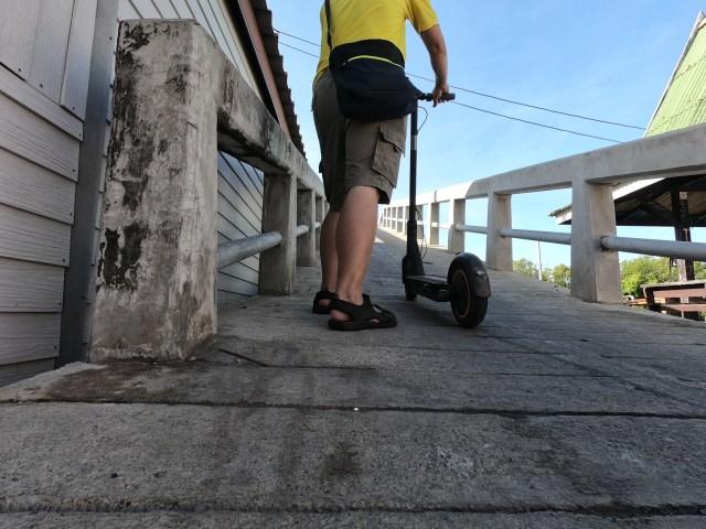 ผู้ชายใส่เสื้อสีเหลือง กางเกงขาสั้น สวมรองเท้าแตะ กำลังเข็นสกู๊ตเตอร์ไฟฟ้าขึ้นสะพานสูงๆ