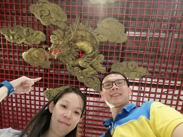 ภาพเซลฟี่ของชายหญิงคู่นึง ที่ถ่ายเงยขึ้นไปที่บนเพดาน มีรูปปั้นมังกรบินอยู่บนเมฆอยู่