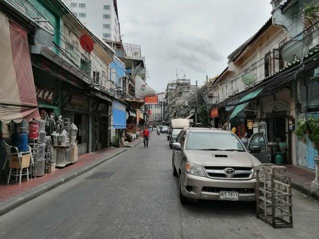 ภาพของถนน มีรถจอดอยู่หลายคันตรงด้านขวาของภาพ มีร้านค้ามากมายอยู่ริมถนน ท้องฟ้าครึ้มๆ