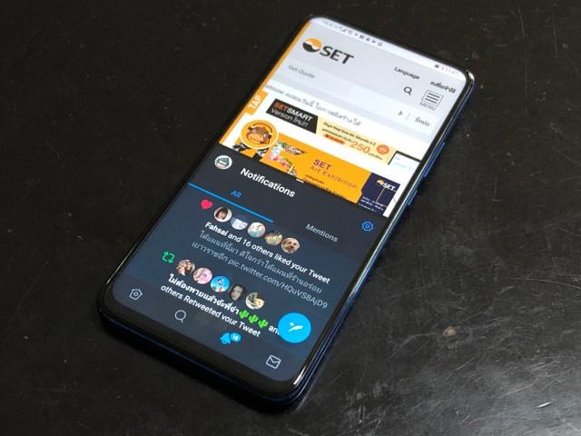 หน้าจอสมาร์ทโฟนกำลังแสดงผลจากสองแอปพร้อมๆ กัน โดยครึ่งบนกำลังแสดงเว็บไซต์ตลาดหลักทรัพย์ ด้านล่างกำลังแสดงแอป Twitter