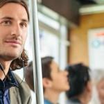 ภาพของผู้ชายต่างชาติ ไว้ผมประบ่า ฟังหูฟัง Plantronics BackBeat Go 410 อยู่ในรถไฟใต้ดิน