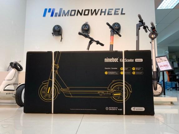 กล่องสกู๊ตเตอร์ไฟฟ้า Ninebot Kickscooter MAX สีดำวางอยู่ด้านหน้าสกู๊ตเตอร์ไฟฟ้ารุ่นต่างๆ บนกำแพงมีชื่อยี่ห้อ MONOWHEEL