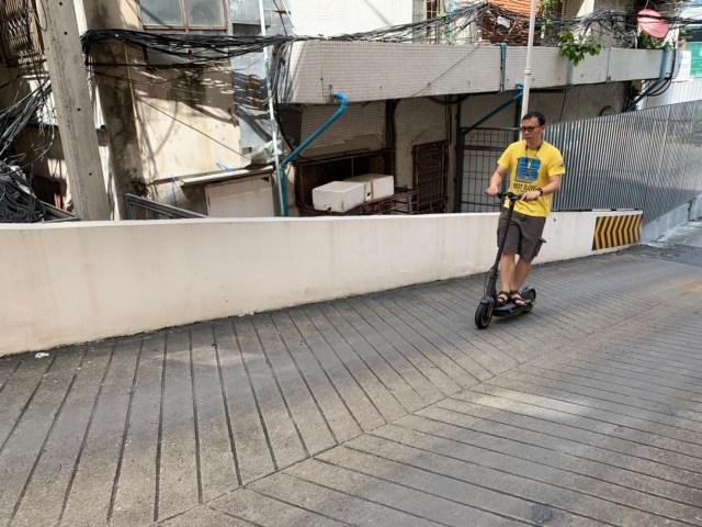 ผมในชุดเสื้อยืดสีเหลือง มีตัวอักษร B สีน้ำเงิน กางเกงสีน้ำตาลเข้ม กำลังขี่สกู๊ตเตอร์ไฟฟ้า Ninebot Kickscooter MAX ขึ้นทางชัน