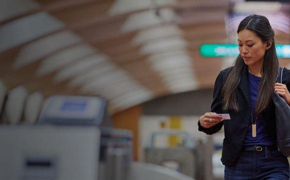 ผู้หญิงในชุดลำลองกำลังเดินอยู่ในสถานีรถไฟใต้ดิน ใส่หูฟัง Plantronics BackBeat Pro 5100
