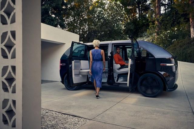 ผู้หญิงผมบลอนด์ใส่ชุดกระโปรงยาวสีน้ำเงิน กำลังเดินไปยังรถตู้ Canoo ที่มีผู้ชายใส่เสื้อแขนยาวสีส้มนั่งรออยู่ในรถ