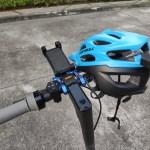 ภาพของสกู๊ตเตอร์ไฟฟ้าส่วนแฮนด์ มีอุปกรณ์เสริมต่างๆ และหมวกกันน็อกจักรยานสีฟ้าวางอยู่