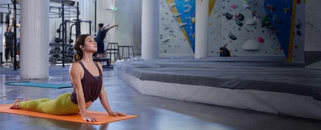 ผู้หญิงชาวต่างชาติ ใส่เสื้อกล้ามสีม่วงน้ำตาล กางเกงสีเขียวมะนาว กำลังเล่นโยคะอยู่บนเสื่อสีส้ม สวมหูฟัง Plantronics BackBeat FIT 3200 อยู่