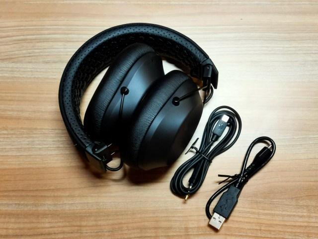 หูฟัง Plantronics BackBeat FIT 6100 ถูกพับเก็บอยู่ ข้างๆ มีสายแปลง Micro USB เป็น Audio 3.5 มม. และ สายชาร์จ Micro USB วางอยู่