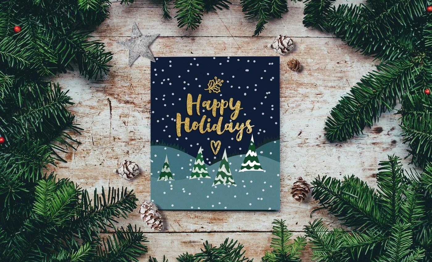 หนังสือชื่อ Happy Holidays วางบนโต๊ะที่มีกิ่งและใบต้นสนวางอยู่รอบๆ เฟรมของภาพ