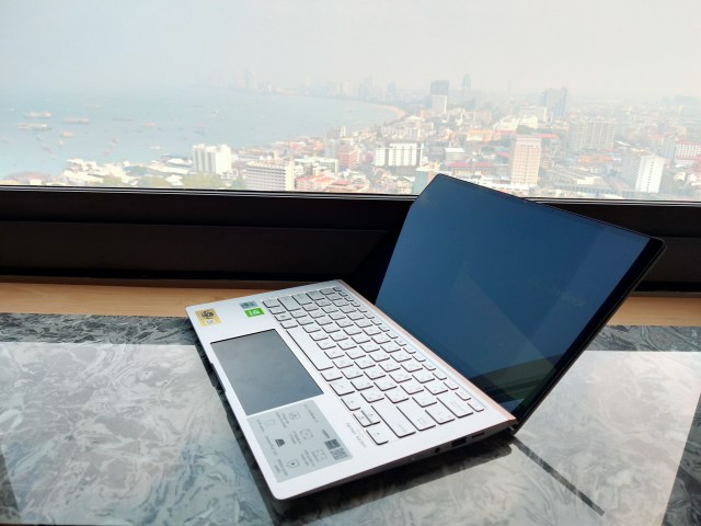 โน้ตบุ๊ก ASUS ZenBook 14 UX434FLC วางอยู่บนโต๊ะริมหน้าต่าง วิวชายหาดจอมเทียน พัทยส