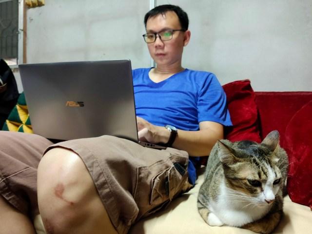 ภาพของตัวผม กำลังนั่งพิมพ์งานบนโน๊ตบุ๊ก ASUS ZenBook 14 UX434FLC ที่วางอยู่บนตัก โดยมีแมวนอนหมอบอยู่ข้างๆ