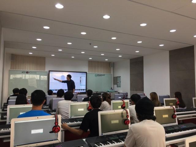 ห้องปฏิบัติการดนตรี ที่มีเครื่องคอมพิวเตอร์และเครื่องดนตรีประเภทอิเล็กโทน นักเรียนกำลังตั้งใจฟังคุณครูที่กำลังสอนอยู่หน้าห้อง
