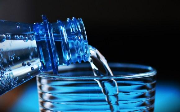 ภาพของขวดน้ำดื่มที่กำลังเทน้ำลงแก้ว