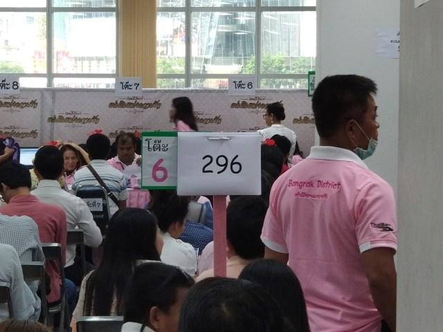 ผู้คนกำลังนั่งรอต่อคิวจดทะเบียนสมรส ป้ายแสดงเลขคิวที่ 296