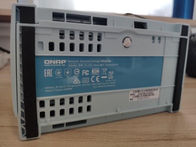 ด้านล่างของ QNAP TS-230 มีข้อความแสดงรายละเอียดของรุ่น และน็อตตัวใหญ่