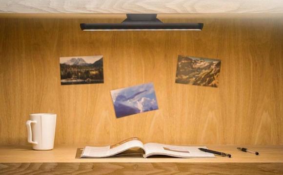 โต๊ะอ่านหนังสือ มีหนังสือ ปากกา แก้วกาแฟ และมีไฟส่องสว่างจากด้านบน