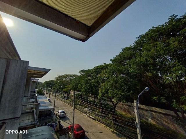 ภาพวิวจากระเบียงบ้าน มองเห็นต้นไม้อยู่ริมรั้วด้านนอก และมีรถยนต์จอดอยู่ริมถนน