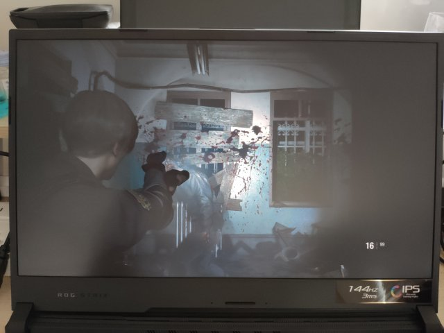จอคอมพิวเตอร์ที่กำลังแสดงภาพจากเกม Resident Evil 2: Remake เป็นตัวละครเอก ตำรวจผู้ชาย กำลังเล็งปืนไปที่ซอมบี้ที่กำลังเดินมาหา