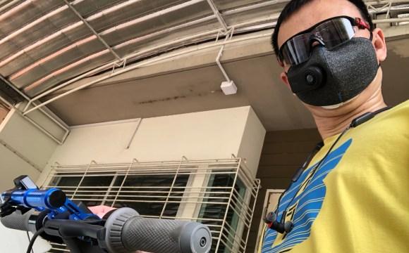 ผู้ชายผมสั้น ใส่แว่นกันแดดและเสื้อยืดสีเหลือง ใส่หน้ากากกันฝุ่น Xiaomi Purely Mask กำลังจับแฮนด์สกู๊ตเตอร์ไฟฟ้า Ninebot Kickscooter MAX