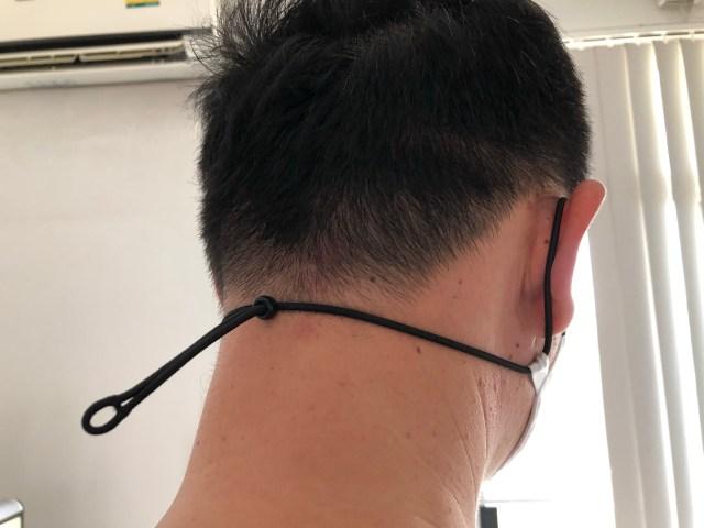 ด้านหลังศีรษะของผู้ชายที่สวมหน้ากากผ้า GQ White แสดงให้เห็นถึงสายรัดที่เกี่ยวหู และอยู่ด้านหลังคอ
