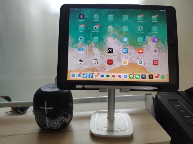 iPad Pro ใส่เคสพร้อมที่เก็บ Apple Pencel กำลังวางอยู่บนขาตั้งสมาร์ทโฟน แท็บเล็ต CHOETECH มีลำโพงไร้สายสีดำวางอยู่ข้างๆ