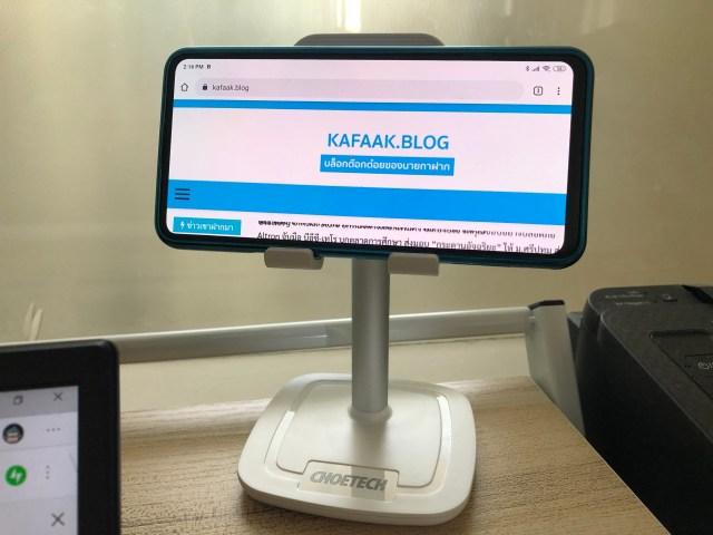 สมาร์ทโฟนสีน้ำเงิน วางอยู่บนขาตั้งสมาร์ทโฟน แท็บเล็ต CHOETEC ในแนวนอน กำลังเปิดหน้าเว็บไซต์ kafaak.blog