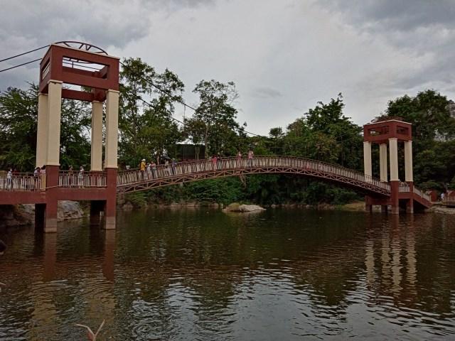 สะพานข้ามทะเลสาบเล็กๆ ในอุทยานหินเขางู สะพานเป็นสีครีมตัดกับสีแดงเลือดหมู ท้องฟ้าครึ้มมีเมฆมาก เหมือนฝนจะตก มีคนอยู่บนสะพานเป็นจำนวนมาก