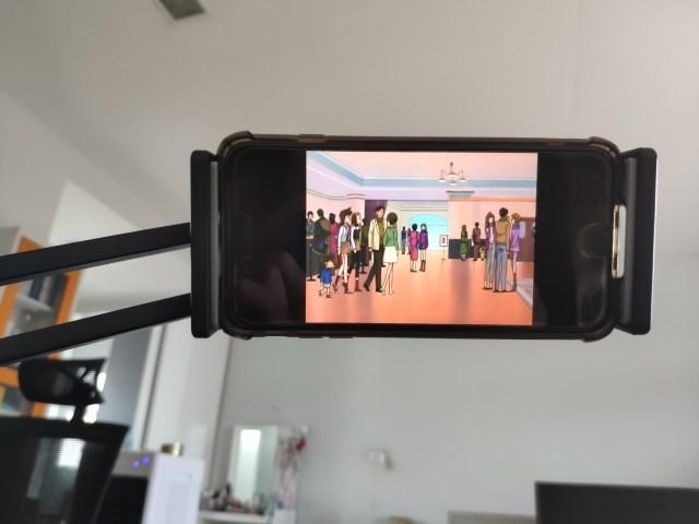 ภาพด้านหน้าของสมาร์ทโฟนที่ถูกจับยึดเอาไว้ด้วย UGREEN Universal Holder with Flexible Long Arm เพื่อดูโคนันระหว่างที่นอนอยู่บนเตียง