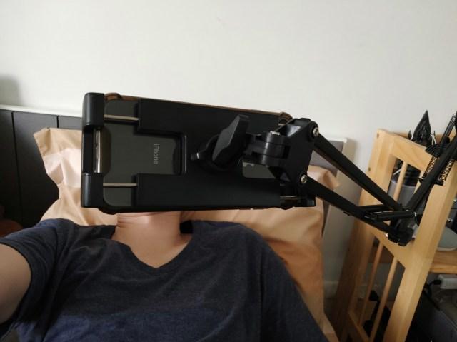 ภาพตัวอย่างการใช้งาน UGREEN Universal Holder with Flexible Long Arm ในการใช้จับสมาร์ทโฟนเพื่อดูคลิป ตอนที่นอนอยู่บนเตียง