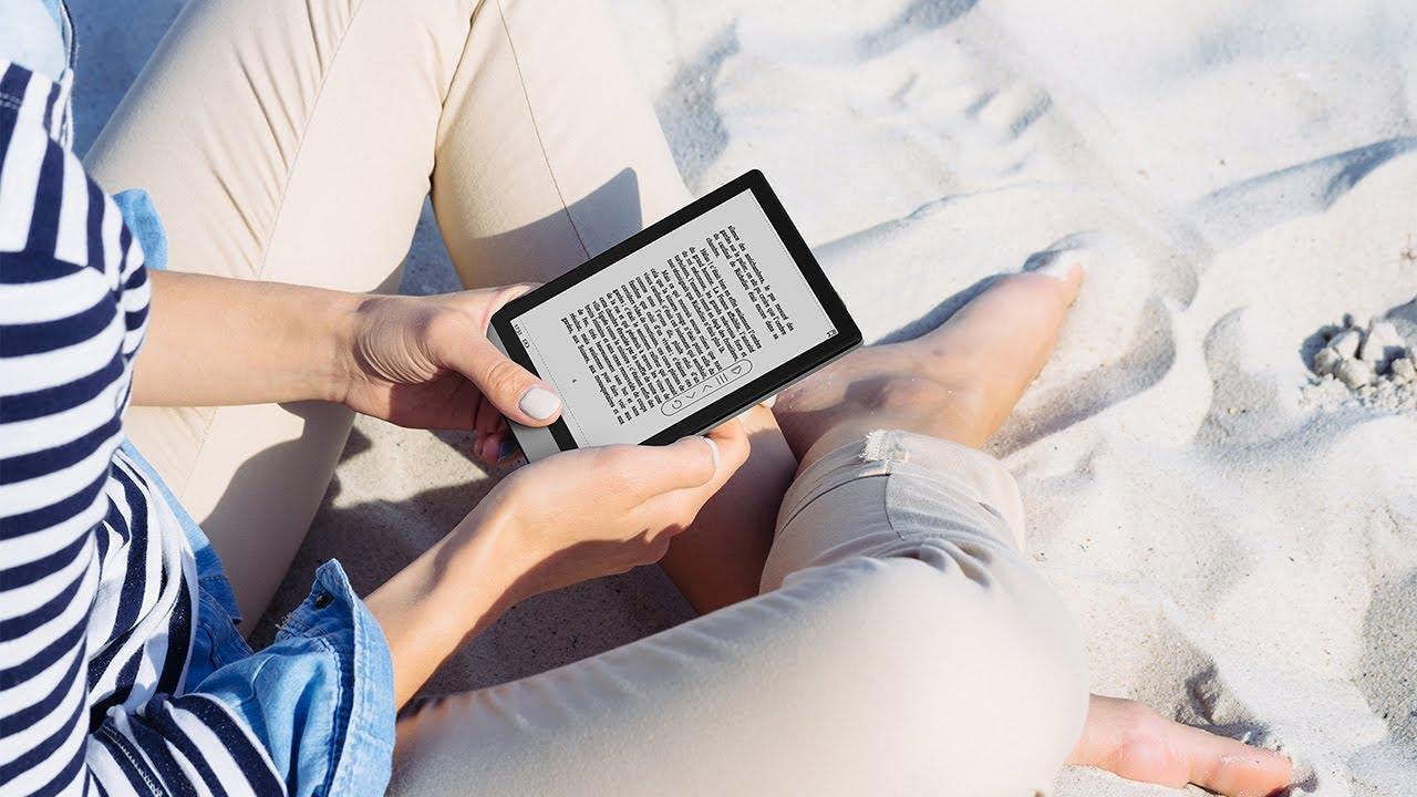 ภาพของผู้หญิงกำลังนั่งอยู่บนพื้นหาดทราย กำลังอ่านอีบุ๊กจาก BOOX POKE 2