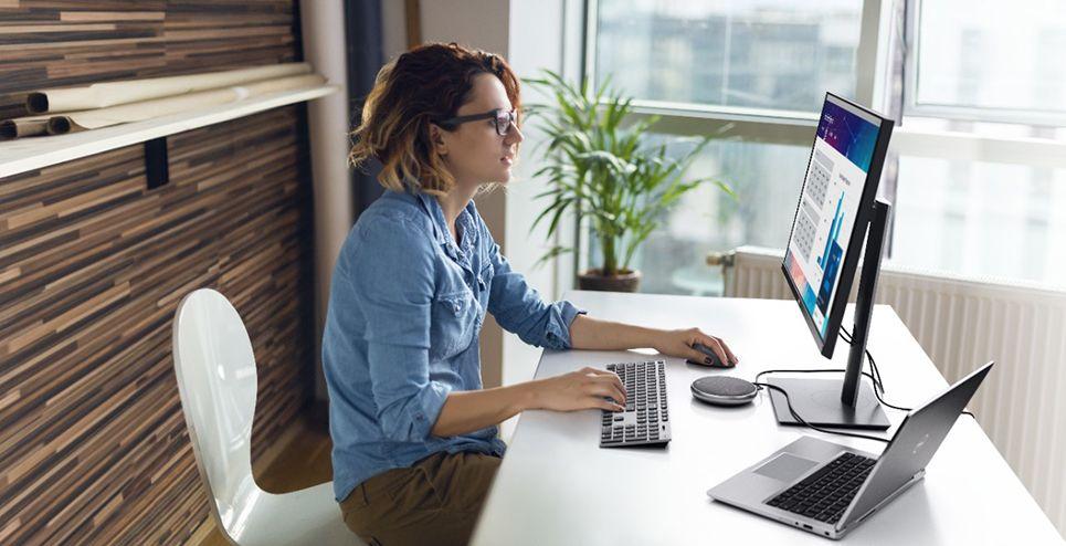 ผู้หญิงผมสีน้ำตาล ไว้ผมสั้น ใส่แว่นตา สวมเสื้อยีนส์สีฟ้า กางเกงสีกากี กำลังสั่งทำงาน ใช้คอมพิวเตอร์โน้ตบุ๊กที่ต่อจอแสดงผลภายนอกอยู่ มือขวาวางบนคีย์บอร์ด มือซ้ายใช้เมาส์