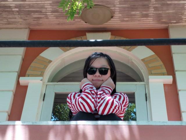 ภาพของผู้หญิงใส่แว่นดำ เสื้อแขนยาวลายสีขาวพาดแดง