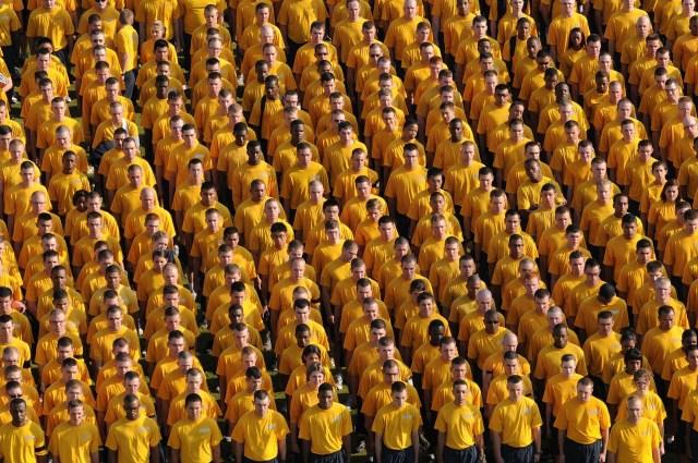 ภาพของกลุ่มคนจำนวนมากยืนเป็นแถว ทุกคนใส่เสื้อสีเหลือง