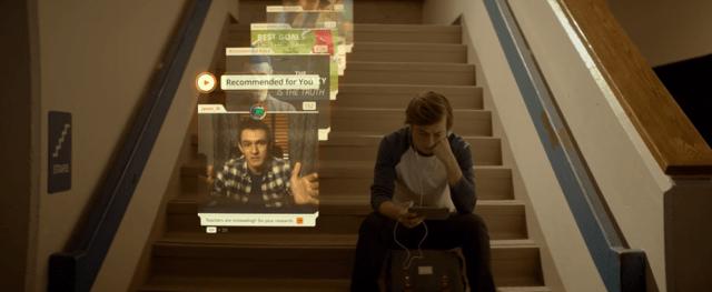 เด็กวัยรุ่นชายอเมริกัน กำลังนั่งอยู่ตรงตีนบันได ดูวิดีโอบนโซเชียลมีเดียจากสมาร์ทโฟนของเขาอยู่