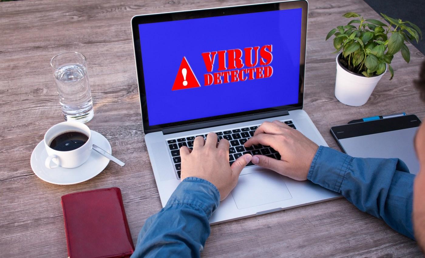 ผู้ชายกำลังใช้งานเครื่อง MacBook อยู่ แต่หน้าจอกลายเป็นสีน้ำเงิน มีตัวอักษรแดงขึ้นว่า Virus detected