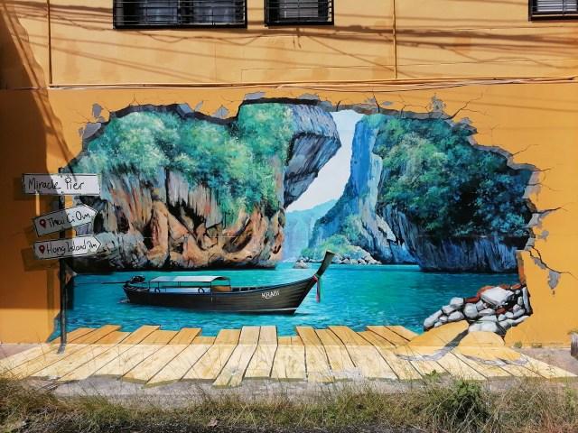 ภาพสตรีทอาร์ตเป็นรูปของเรือหางยาวลอยอยู่บนทะเลโดยมีเกาะเป็นแบ็กกราวด์
