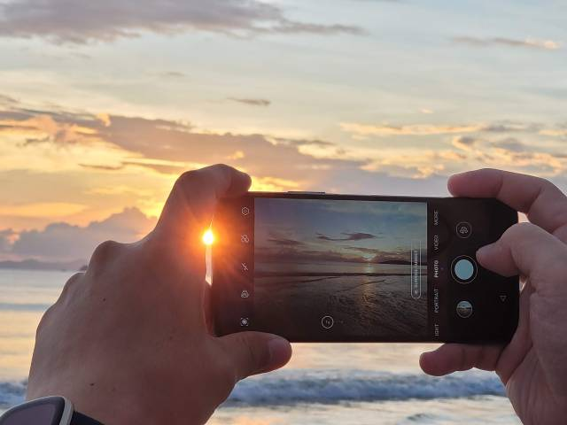 มือกำลังยกสมาร์ทโฟนขึ้นมาถ่ายภาพวิวทะเลในยามพระอาทิตย์ตกดิน