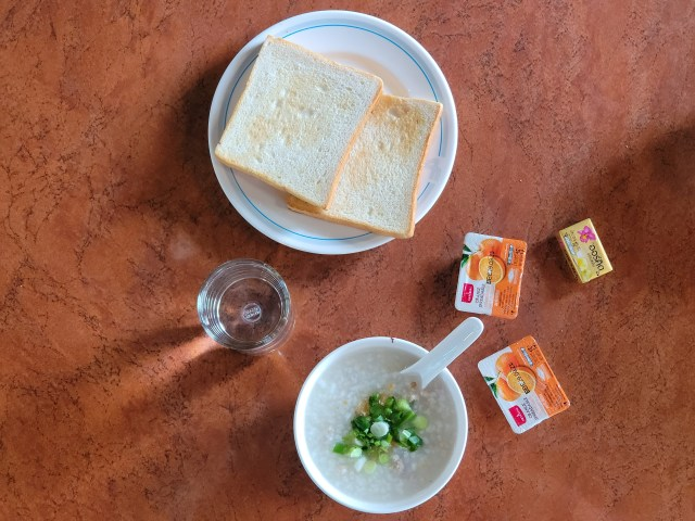 อาหารเช้าของโรงแรม Friday ประกอบไปด้วย ข้าวต้มหมู ขนมปังปิ้ง แยมส้มและเนยออร์คิด