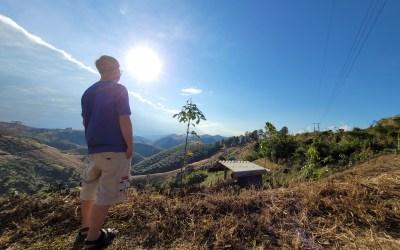 ผู้ชายใส่เสื้อสีน้ำเงิน กางเกงขาสั้น กำลังยืนหันหน้าเข้าหาดวงอาทิตย์ มองไปที่วิวภูเขา