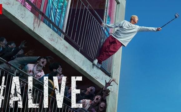 โปสเตอร์หนังเรื่อง #ALIVE คนเป็นฝ่านรกซอมบี้ เป็นภาพของผู้ชายใส่เสื้อยืดแขนยาวสีขาว กางเกงสีแดง กำลังยืนเกาะลูกกรงระเบียง พยายามยื่นสมาร์ทโฟนและไม้เซลฟี่ออกไปเพื่อรับสัญญาณมือถือ