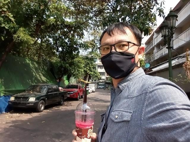 ภาพเซลฟี่ของผู้ชายใส่แว่น ผมสั้น สวมหน้ากากผ้า ถือแก้วพลาสติกอยู่ในมือข้างหนึ่ง ถ่ายในบริเวณซอยแห่งหนึ่ง
