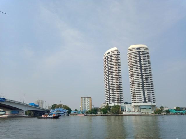 ภาพของอาคารคอนโดมิเนียมริมแม่น้ำเจ้าพระยา มีเรือข้ามฟากวิ่งอยู่ในแม่น้ำ และเห็นส่วนหนึ่งของสะพานพระปิ่นเกล้า