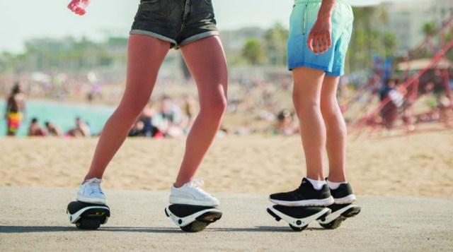 ภาพถ่ายช่วงขาของผู้หญิงสองคน ใส่กางเกงขาสั้น กำลังใช้งานสเก็ตไฟฟ้า Segway Drift W1 อยู่บนถนนริมหาดทราย