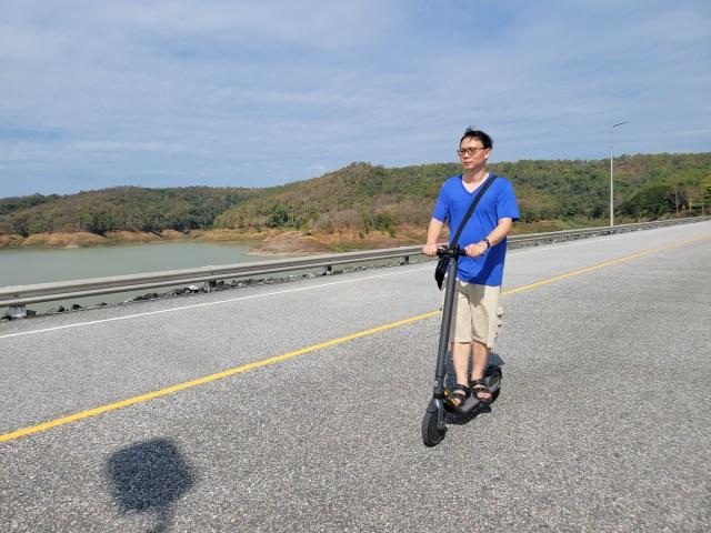 ผู้ชายผมสั้น ใส่แว่น สวมเสื้อยืดคอวีสีฟ้า กางเกงขาสั้นสีกากี กำลังขี่สกู๊ตเตอร์ไฟฟ้า Ninebot Kickscooter E25 อยู่บนถนนบนสันเขื่อน