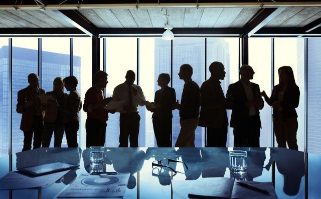 ภาพเงาของผู้คนที่จับกลุ่มคุยกันอยู่ริมหน้าต่างของตึก โดยมีโต๊ะประชุมวางอยู่ด้านหน้า