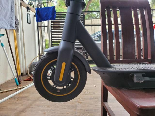 ภาพระยะใกล้ของ Ninebot Kickscooter MAX ตรงส่วนล้อหน้า ตัวสกู๊ตเตอร์ถูกวางไว้บนเก้าอี้ไม้ส