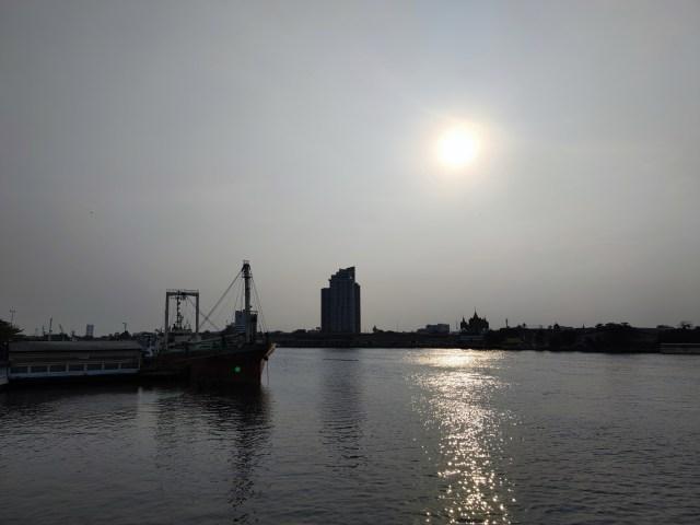 ภาพวิวแม่น้ำเจ้าพระยา ด้านซ้ายเห็นเรือขนสินค้าจอดอยู่ ด้านขวาเป็นบ้านเรือนและคอนโด