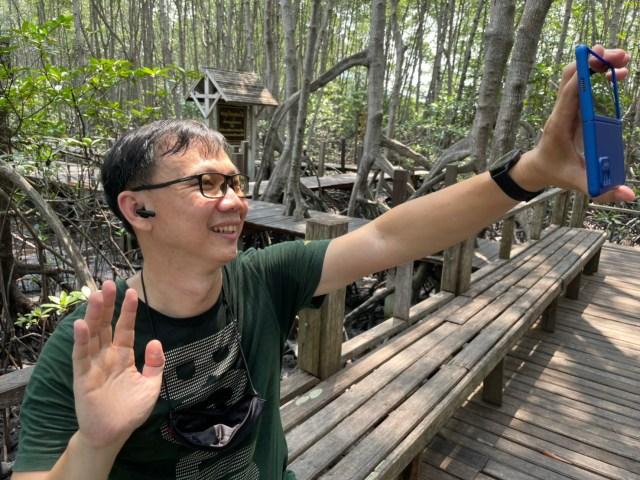 ผู้ชายผมสั้นใส่แว่น สวมเสื้อยืนคอกลมสีเขียว กำลังทำ Video call ผ่านสมาร์ทโฟน และหูฟัง Huawei FreeBuds 4i